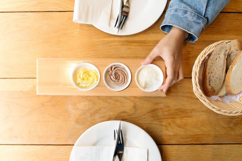 Fördelande smör för kvinnahand på skivat bröd royaltyfria foton