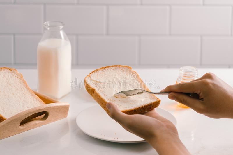 Fördelande smör för man på skiva av bröd, closeup fotografering för bildbyråer