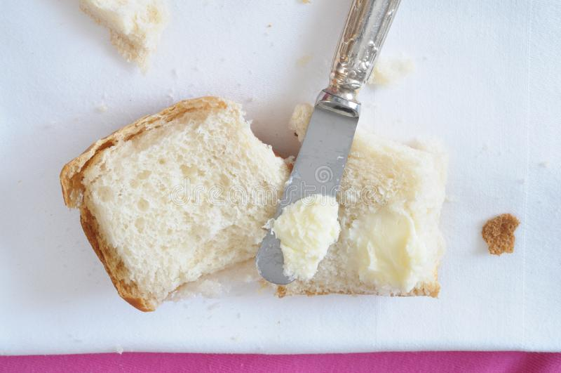 Fördelande smör på bröd, direkt över royaltyfri bild