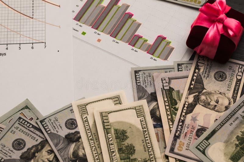 Fördelning av pengar, den finansiella planläggningen, dollar i kuvert och en gåvaask med en rosa pilbåge royaltyfri bild