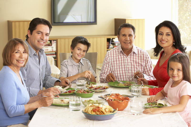 Fördjupad latinamerikansk familj som hemma tycker om mål arkivbild