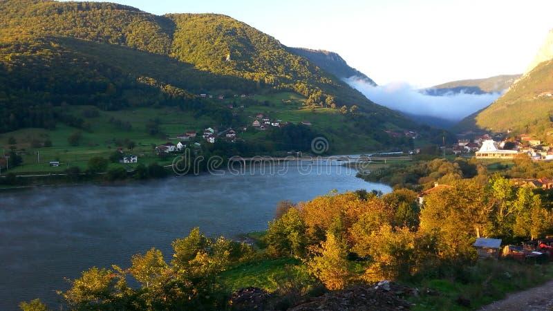Fördunkla bron, och sjön true en soluppgång royaltyfri foto
