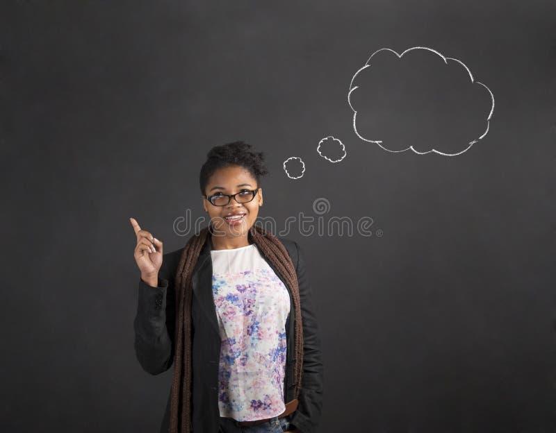 Fördunklar bra idétanke för den afrikanska kvinnan på svart tavlabakgrund royaltyfri bild
