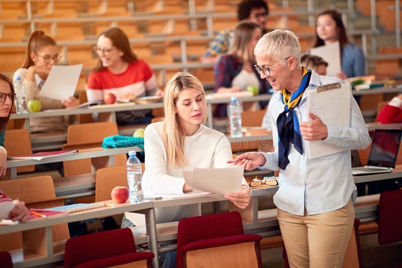 Föreläsare med flickastudenten i en examen i ett klassrum arkivfoton