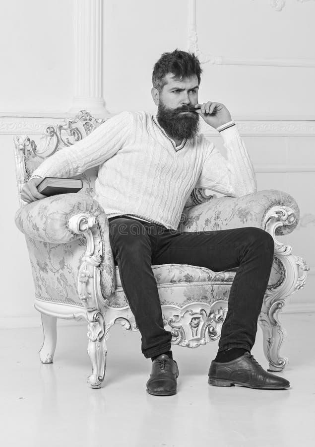Föreläsaren sitter på fåtöljen, och håll bokar, vit väggbakgrund Forskare professor på fundersam framsidaanalysering royaltyfri foto