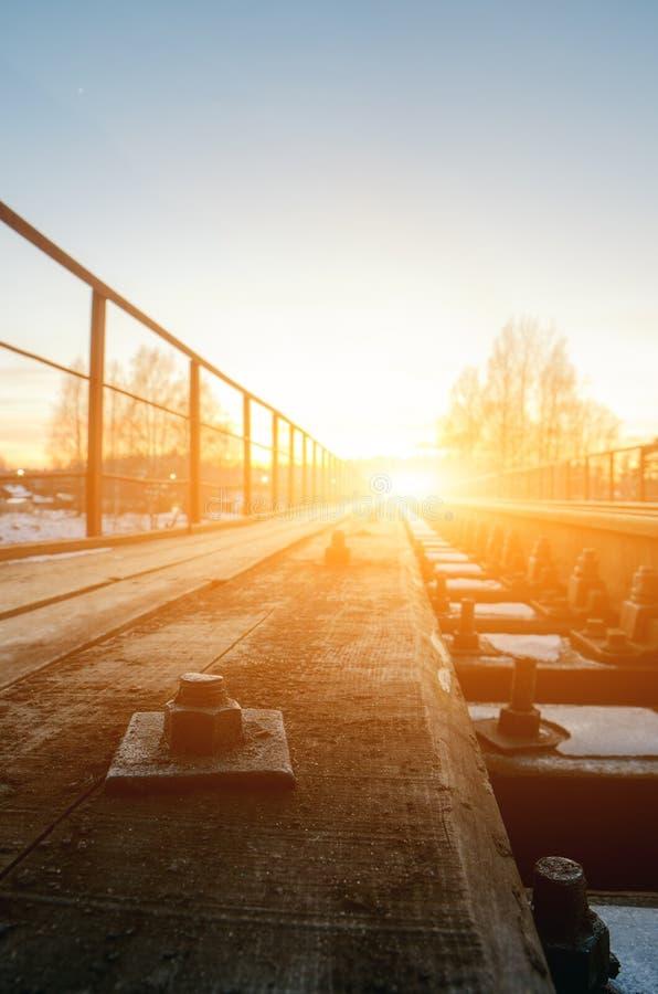 Föreningspunkt av järnvägspåret i drevstation mot härligt ljus av fastställt himmelbruk för sol för landtransport och logistisk b royaltyfria bilder