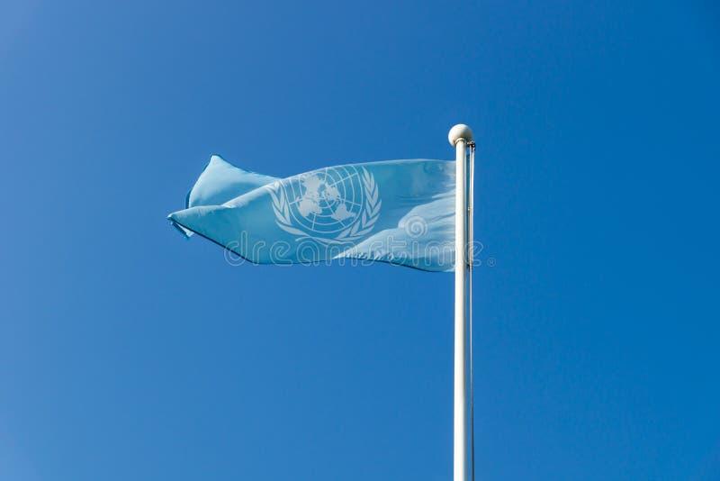 Förenta NationernaFN-flagga som vinkar på molnfri blå himmel på Förenta Nationerna minnes- kyrkogård, Busan, Sydkorea royaltyfria bilder