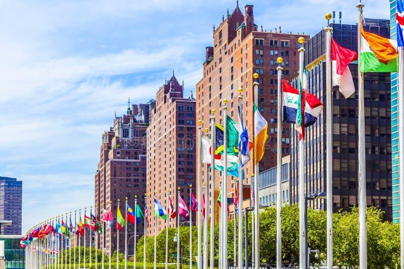 Förenta Nationernahögkvarter med flaggor av medlemmar av FN arkivfoto