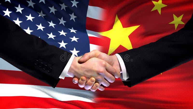 Förenta staterna- och Kina handskakning, internationellt kamratskap, flaggabakgrund arkivfoto