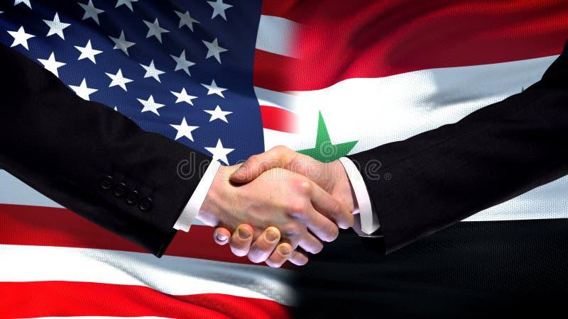 Förenta staterna- och Syrien handskakning, internationellt kamratskap, flaggabakgrund arkivfoto