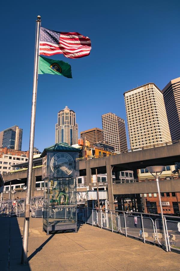 Förenta staterna och Washington State-flaggan som viftar över Colman Clock i Seattle, Washington, Förenta staterna arkivfoton
