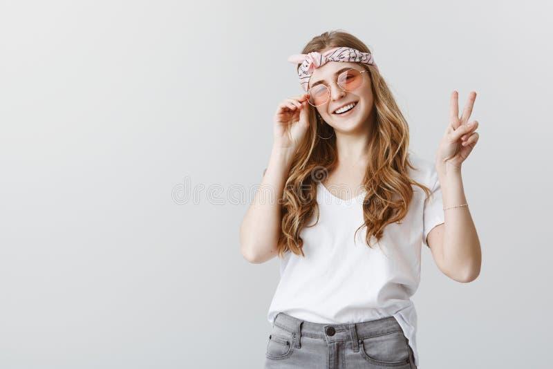 Föreställ allt bosatt liv för folk i fred Stående av den bekymmerslösa stilfulla unga kvinnan i huvudbindel och moderiktig solgla arkivfoto