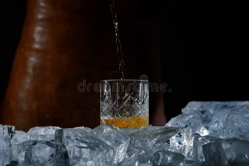 Föreställa exponeringsglas, whiskystrålen, stora bitar av is royaltyfri foto