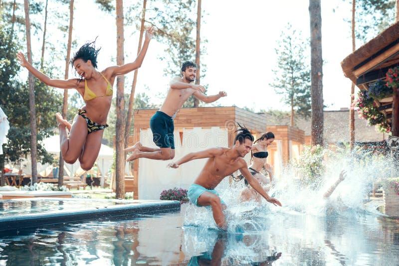 Företag av lyckliga ungdomarsom hoppar i tips som bildar färgstänk Begrepp för simbassängparti arkivfoto