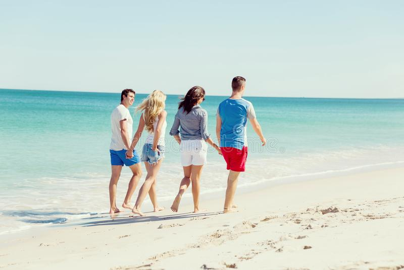 Företag av ungdomarpå stranden royaltyfri fotografi