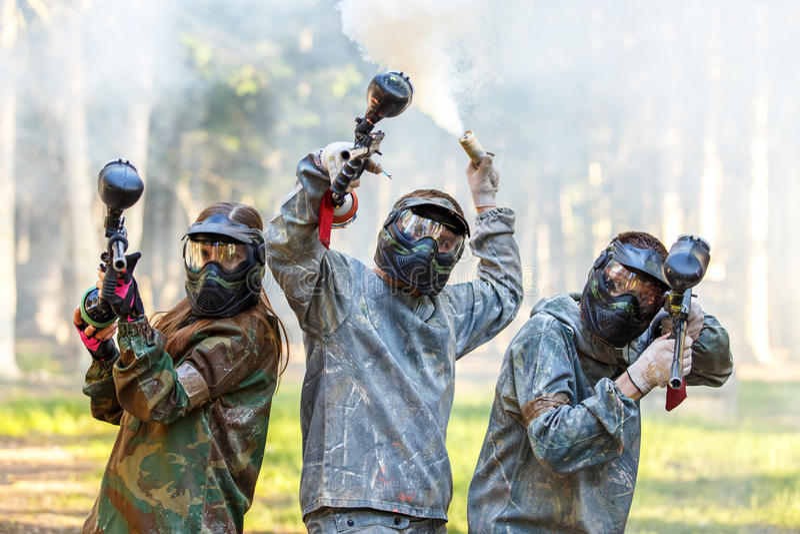 Företag av vänner som poserar med vapen för rökgranat och paintball fotografering för bildbyråer