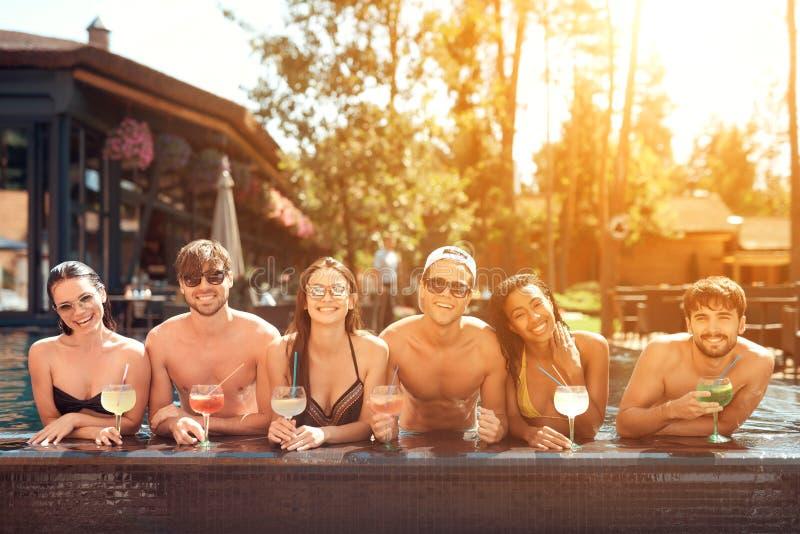 Företaget av lyckliga vänner dricker coctaildrinkar i pöl på sommartid Simbassängparti royaltyfria bilder