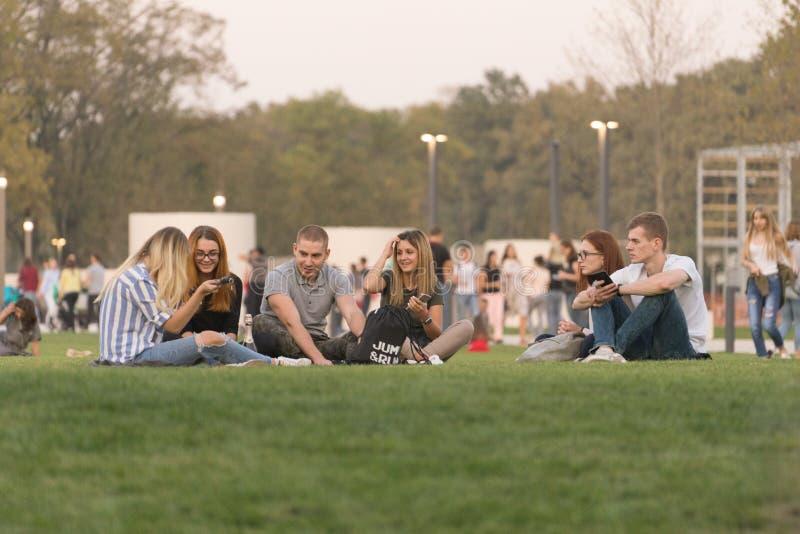 Företaget av ungdomarsom sitter på den gröna gräsmattan på öppningen av ett nytt modernt, parkerar i staden i hösttiden av året royaltyfria foton