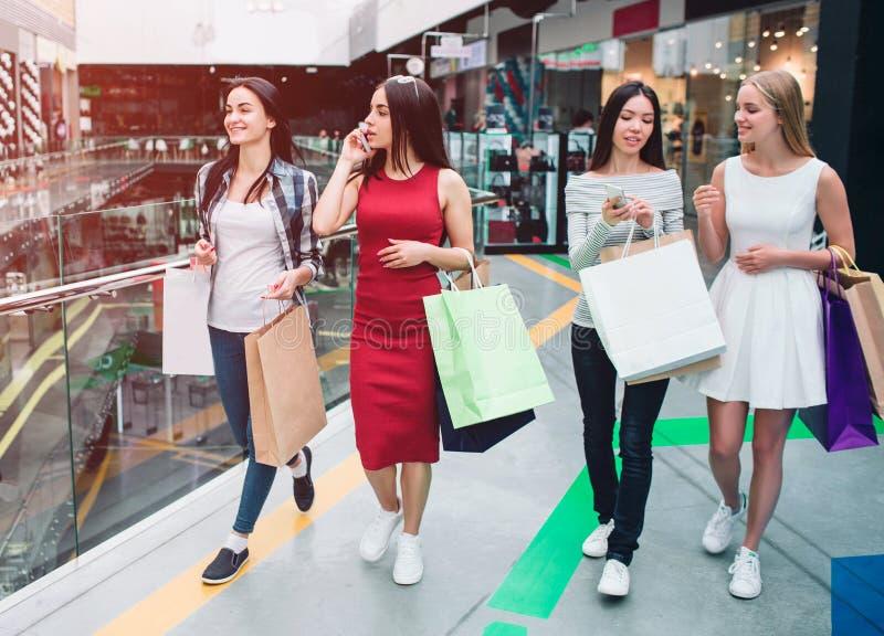 Företaget för kvinna` s är i galleria De delas på två grupper Flickan i röd klänning talar på telefonen, medan den asiatiska flic arkivbilder