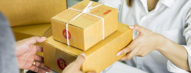 Företagsägaren för startarbetearbetsplatsen förbereder sig att leverera gods i kartong till leveransmannen, som har räckt över, b fotografering för bildbyråer