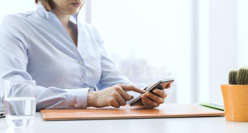 Företags affärskvinna som arbetar och förbinder med hennes smartphone fotografering för bildbyråer