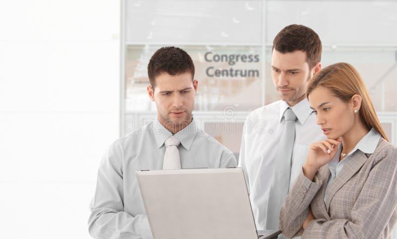 Företags folk som ser bärbar datorskärmen arkivbild