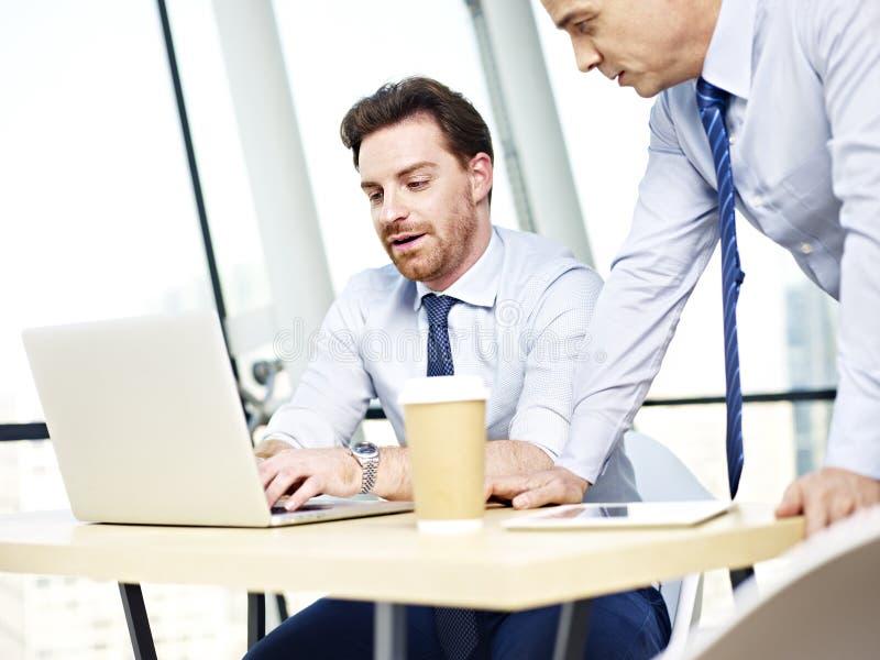 Företags folk som tillsammans arbetar på bärbar datordatoren royaltyfria bilder