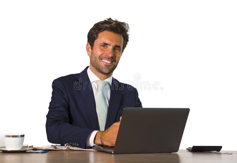 Företags isolerad stående för företag av den unga stiliga och attraktiva affärsmannen som arbetar på skrivbordet för kontorsbärba royaltyfria foton
