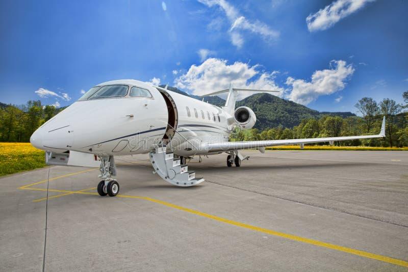 Företags privat jet på landningsbana i berg royaltyfri bild