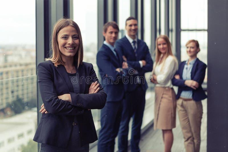 Företags stående av den unga affärskvinnan med hennes kollegor i bakgrund fotografering för bildbyråer
