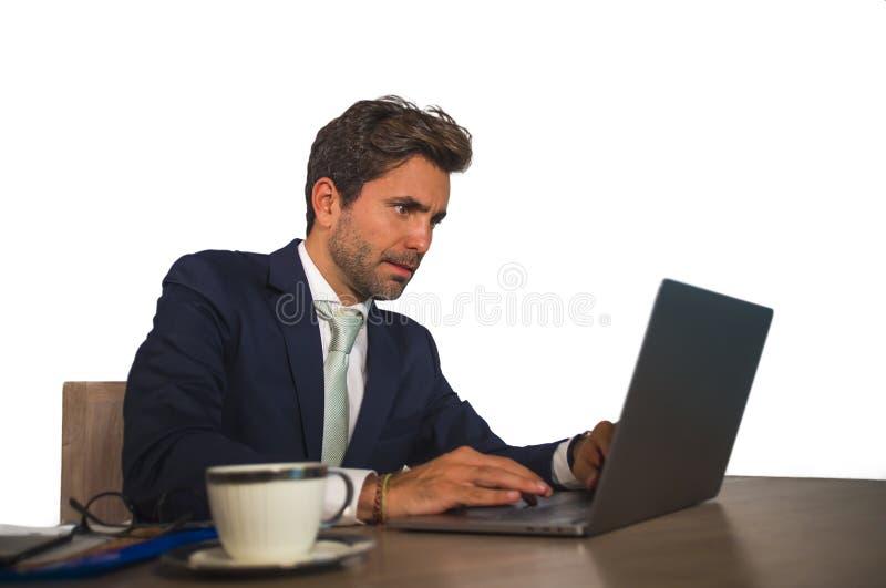 Företags stående av den unga attraktiva och effektiva affärsmannen som arbetar på skrivbordet för kontorsbärbar datordator som är royaltyfri fotografi