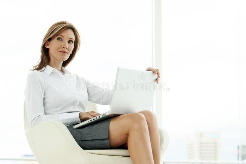 Företags utövande kvinna som använder bärbara datorn i modernt läge fotografering för bildbyråer