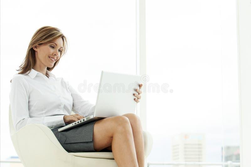 Företags utövande kvinna som använder bärbara datorn i modernt läge royaltyfri bild