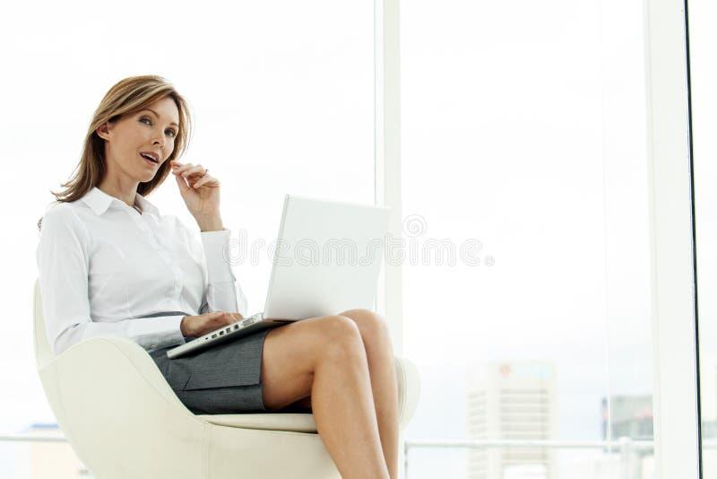 Företags utövande kvinna som använder bärbara datorn i modernt läge royaltyfri foto