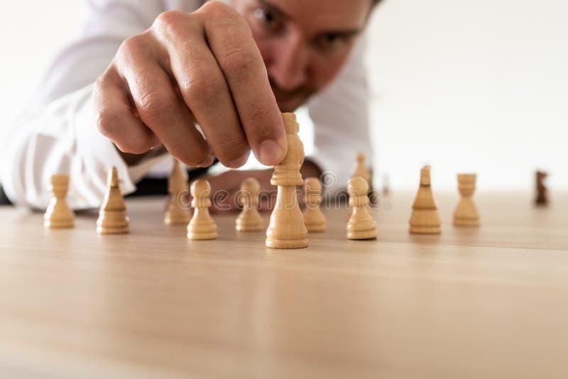 Företagsledare som ordnar schackstycken med konung i den ledande positionen royaltyfri bild
