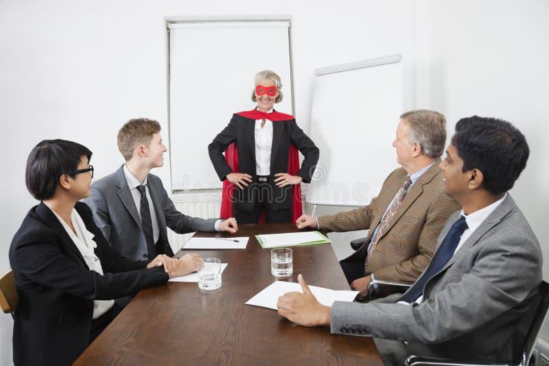 Företagsledare som superhero framme av kollegor på mötet i konferensrum arkivfoto