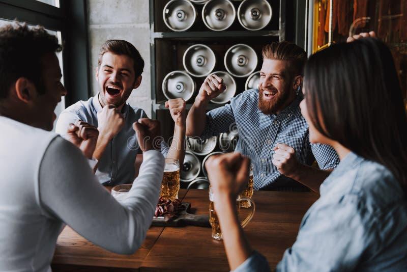 Företagsvänner som firar dricka öl i bar royaltyfri fotografi