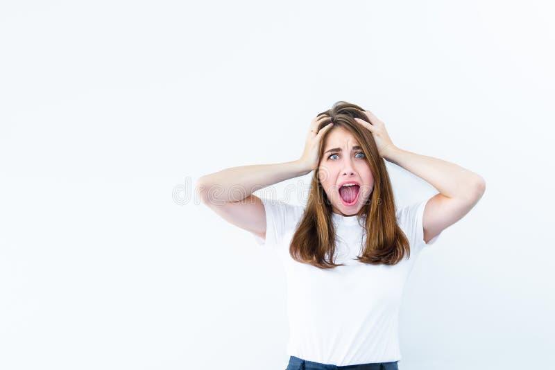 Förfärligt spänning, chock Den unga emotionella förvånade kvinnan ser kameran som knäpper fast huvudet i händer och öppnar hennes arkivfoto