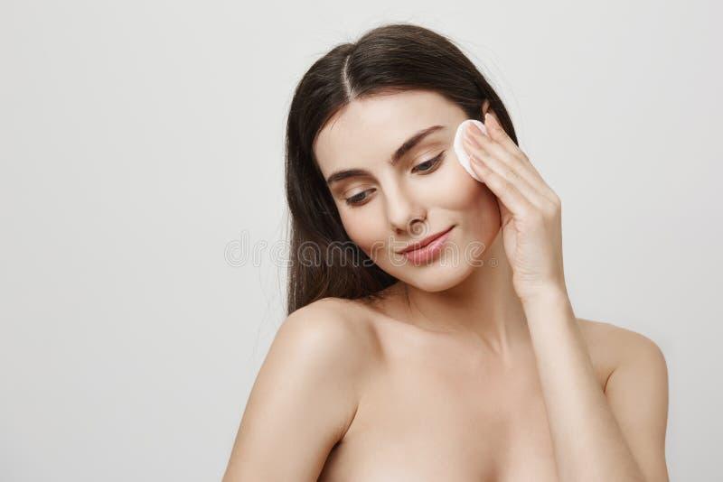 Förfölja skönhet Inomhus skott av det charmiga unga europeiska kvinnliga anseendet i badrum, medan torka hud med bomullsblocket fotografering för bildbyråer