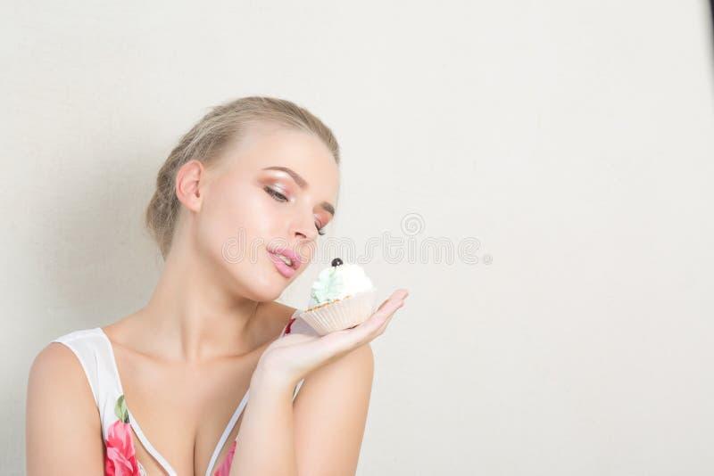 Förförisk blond dam som poserar med den aptitliga efterrätten med kräm fotografering för bildbyråer