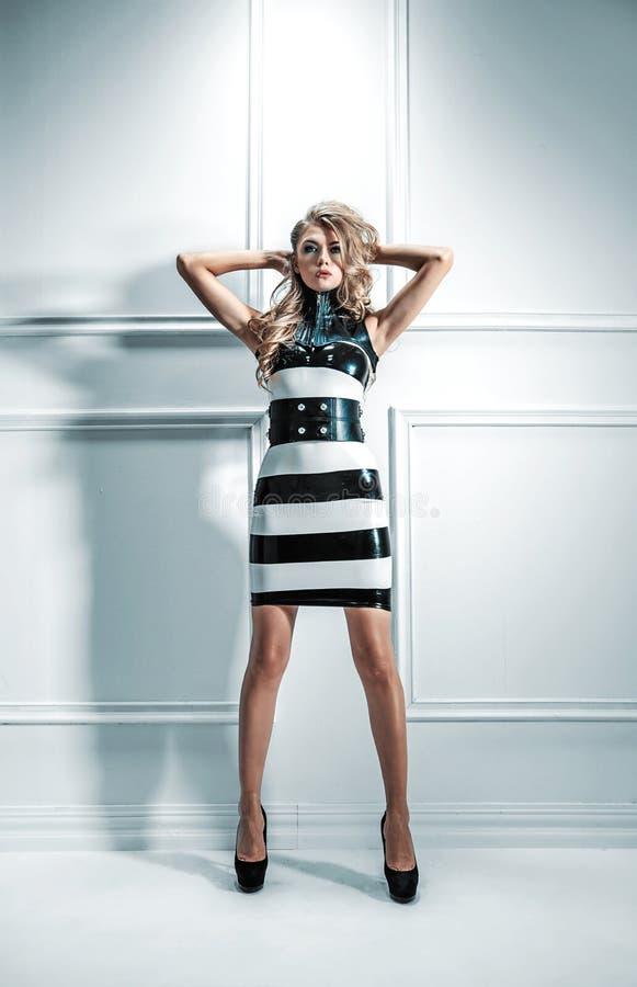 Förförisk blond kvinna som bär en latexklänning royaltyfria bilder