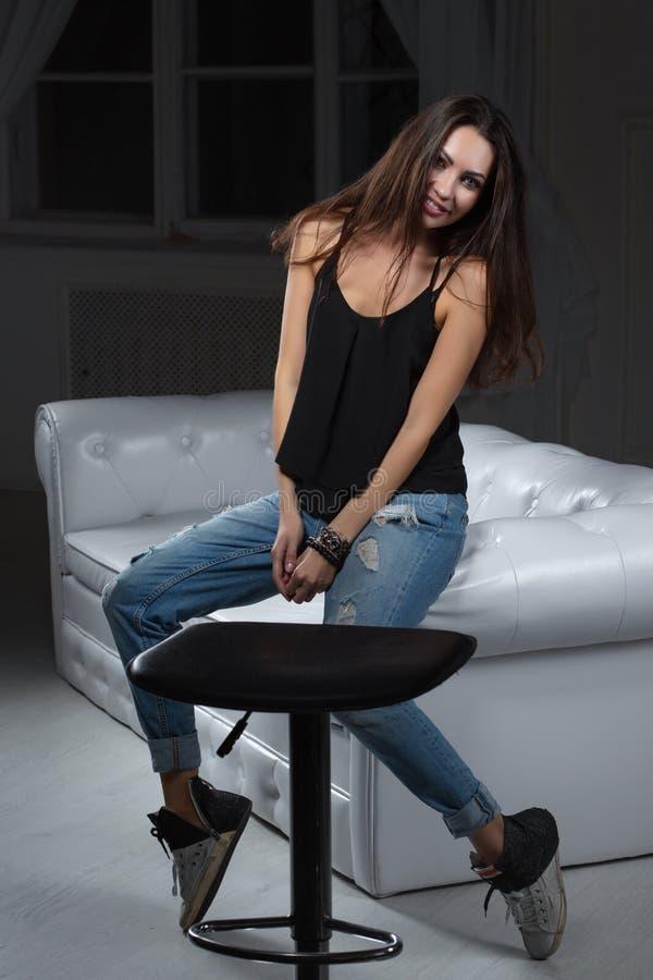 Förförisk brunett som poserar att sitta på en soffa royaltyfria foton