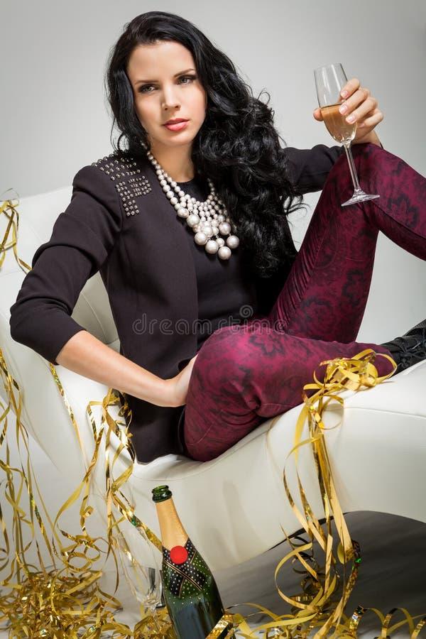 Förförisk brunett som rymmer ett exponeringsglas av champagne arkivfoton