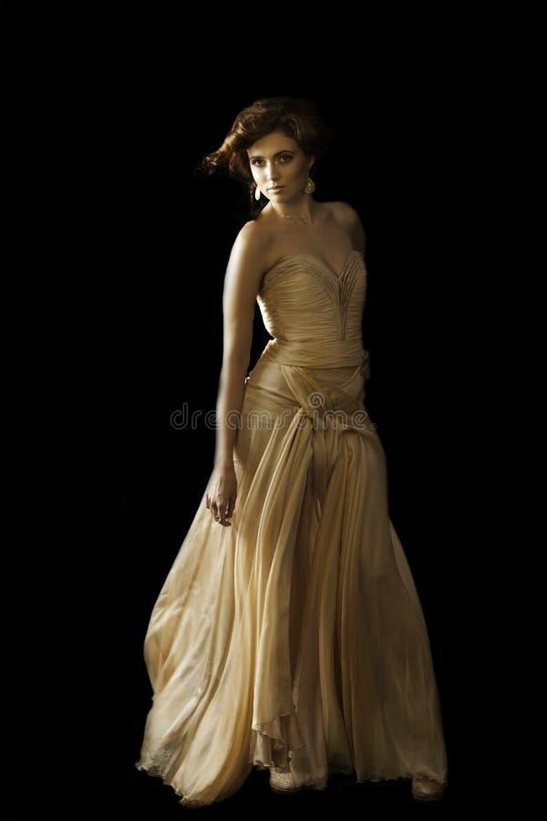 Förförisk brunettkvinna i sömnadaftonklänning arkivfoto