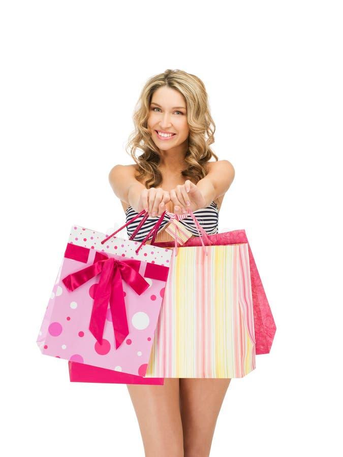 Förförisk kvinna i bikini med shoppingpåsar royaltyfri bild
