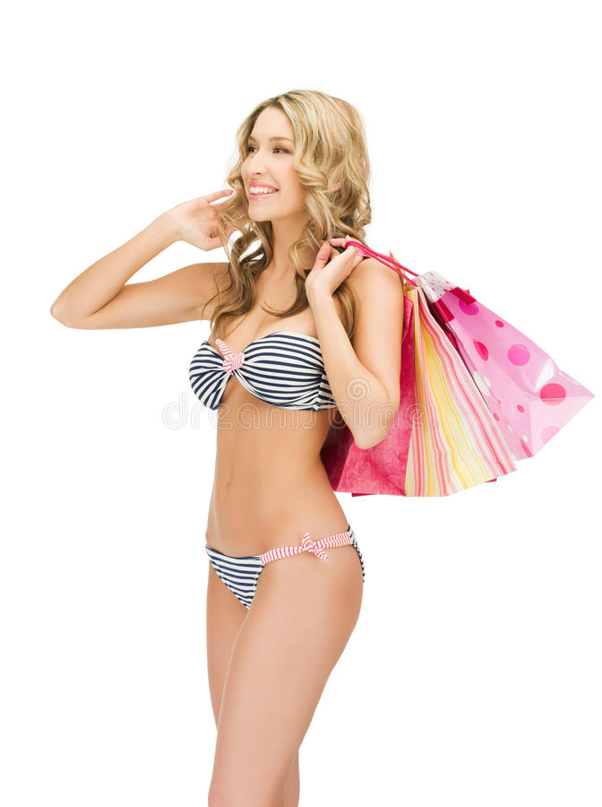 Förförisk kvinna i bikini med shoppingpåsar royaltyfri foto