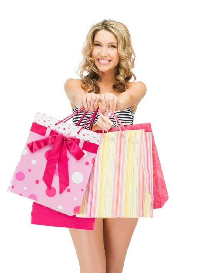 Förförisk kvinna i bikini med shoppingpåsar fotografering för bildbyråer