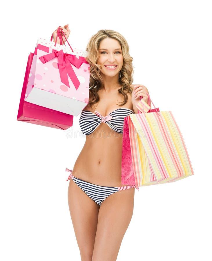 Förförisk kvinna i bikini med shoppingpåsar royaltyfri fotografi