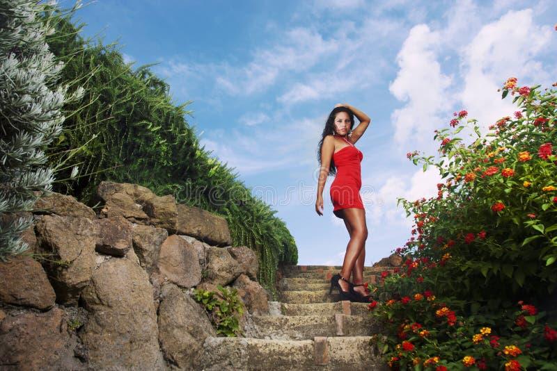 Förförisk kvinna i röd klänning royaltyfri foto