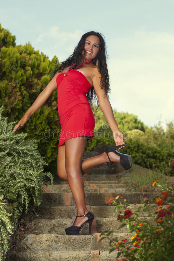 Förförisk kvinna i röd klänning som ler trycka på hennes stiletthäl royaltyfri bild